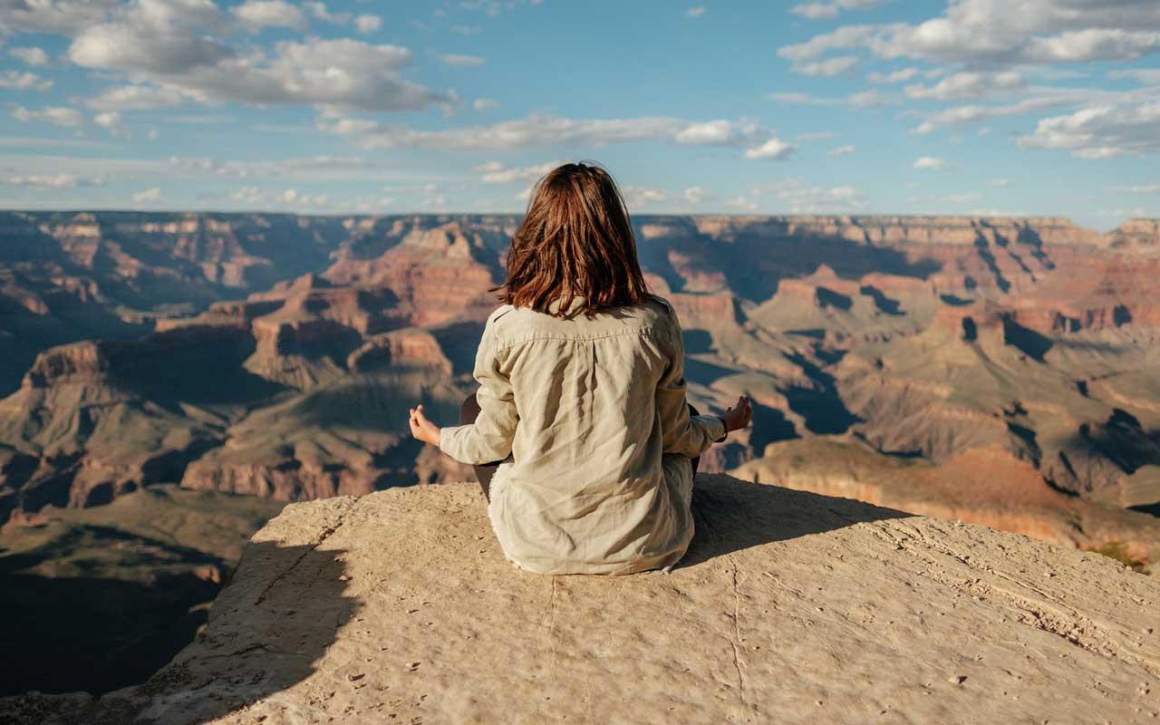 A woman meditates outside at the Grand Canyon.