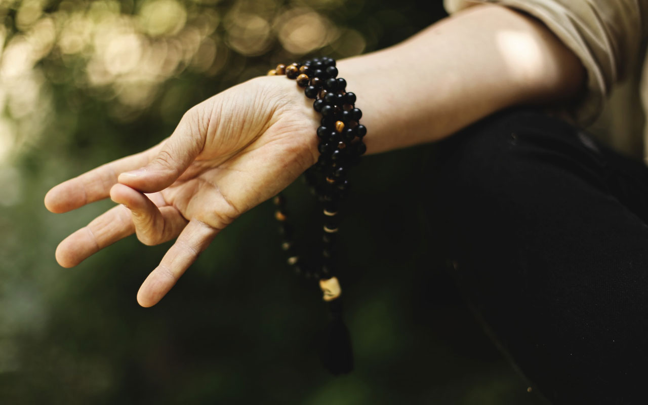 A person wearing mala beads around their wrist makes a mudra (hand gesture) while meditating.