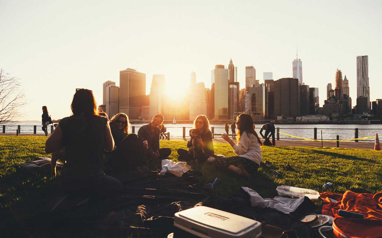 A group of friends has an outdoor picnic by the waterside. Socializing with friends has positive effects on memory.