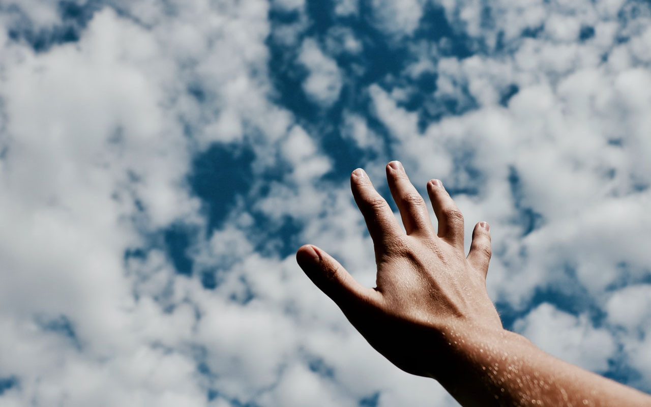 A hand reaches into a partially cloudy sky. Letting go of outcomes is a good concentration exercise.