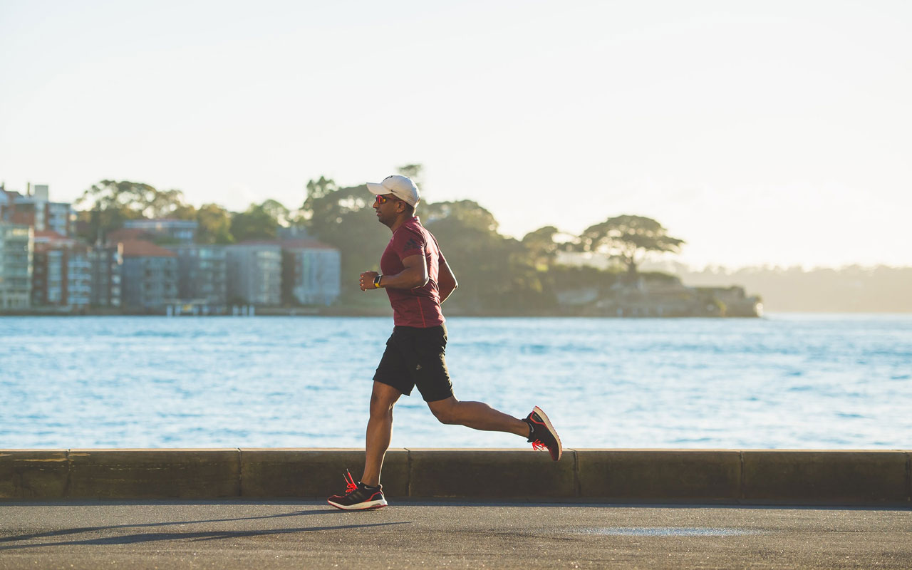 A person runs along a body of water. Keeping healthy through regular exercise is a key part of your memory strategy.