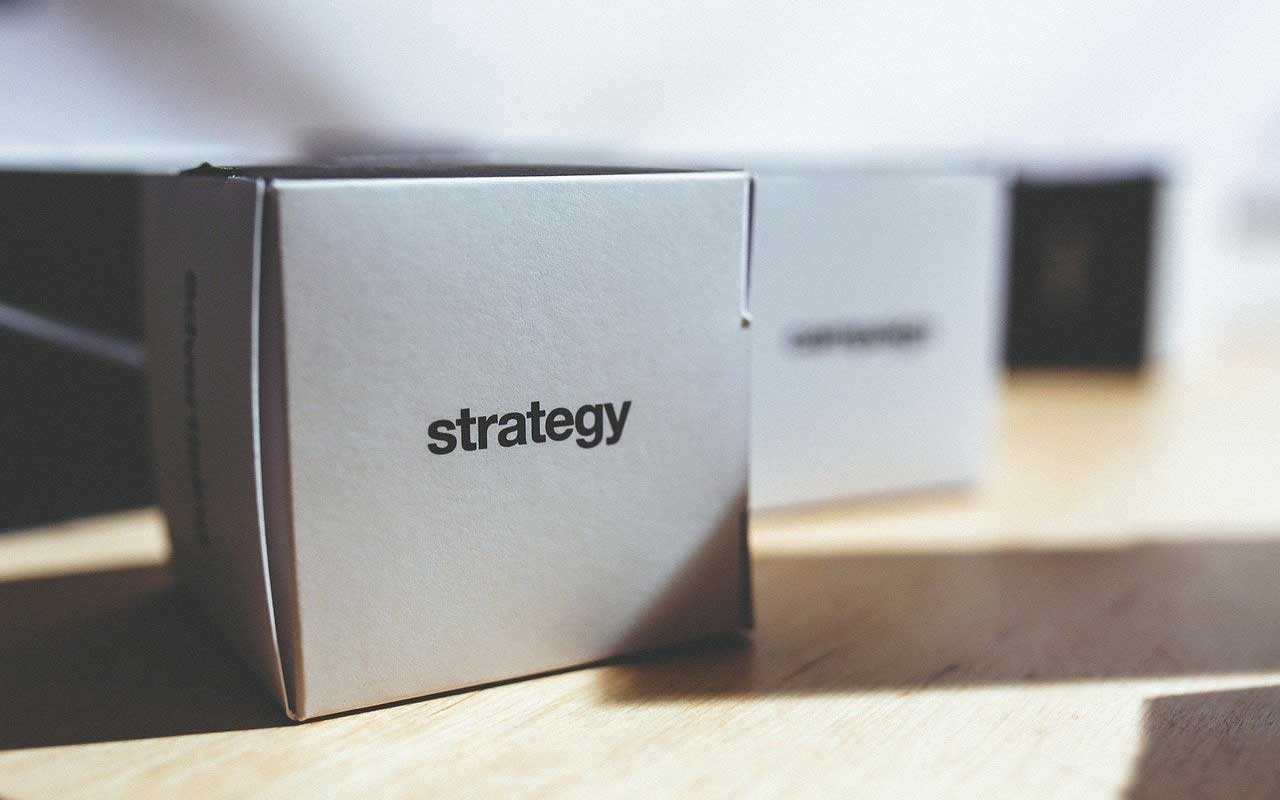 "A set of paper ""dice"" with the word strategy printed on the side."