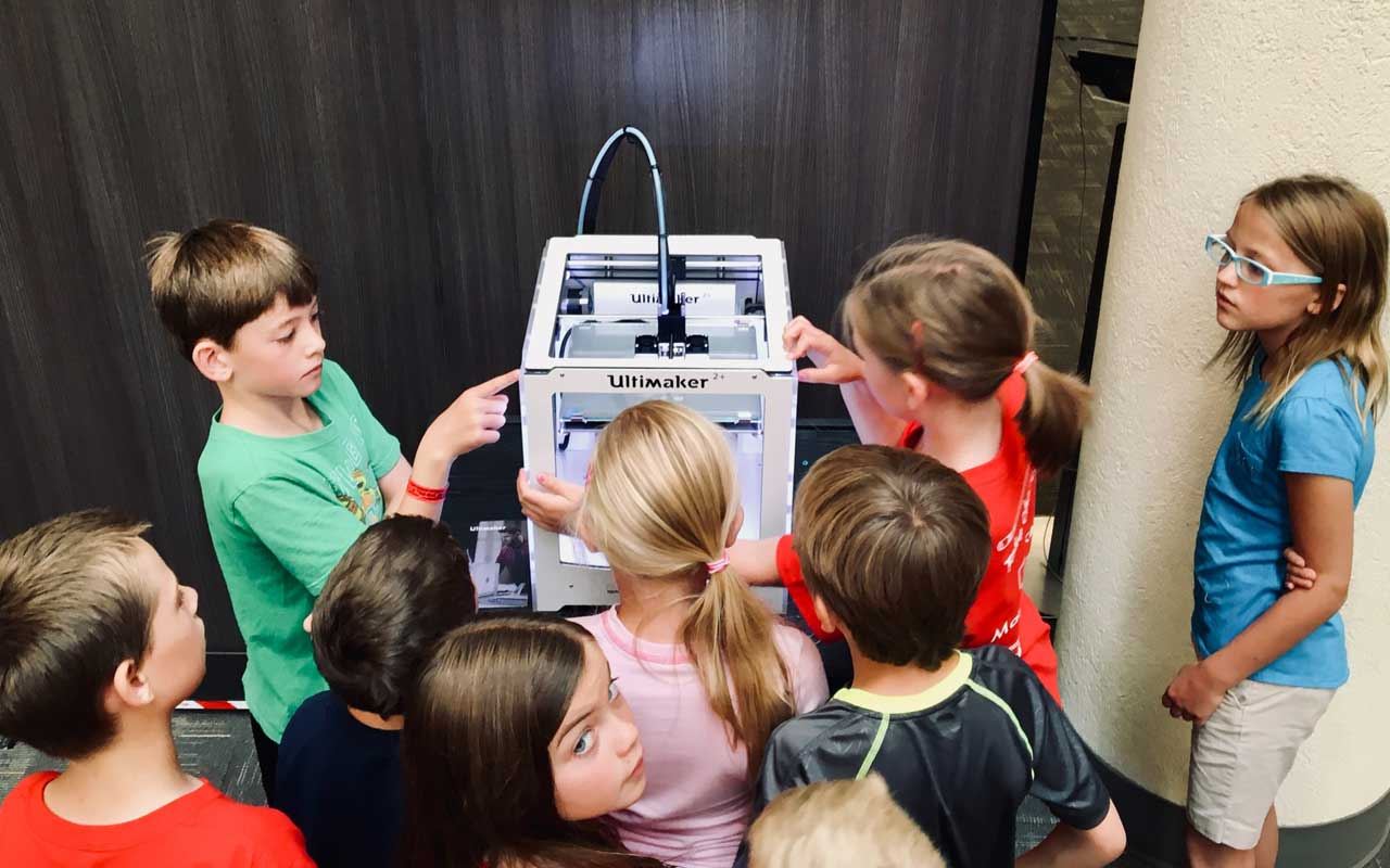 Students gather around a 3D printer, an example of creative problem-solving.