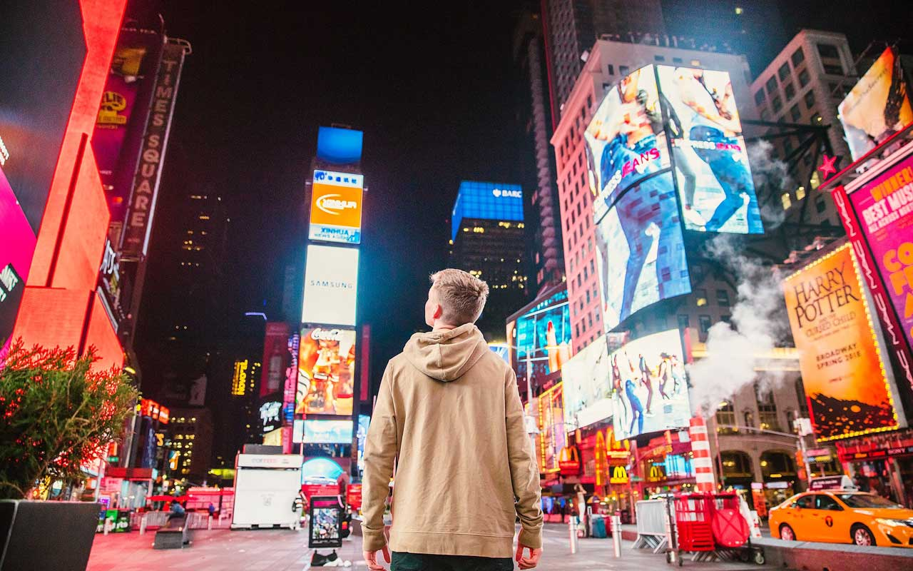 A young person stands in the middle of Times Square in New York City, surrounded by advertisements. Eliminating ads from your life can help you improve concentration.