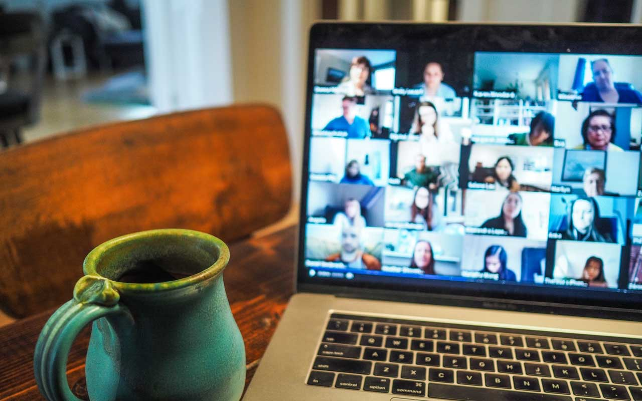 A mug of tea sits next to a laptop showing a group video conference. Study groups and accountability partners may not meet in person due to health concerns due to the pandemic.
