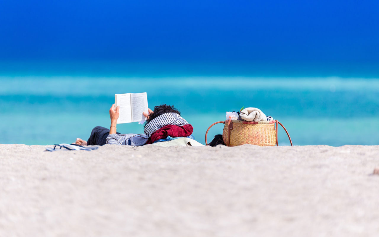 A person relaxes on the beach with a book, possibly helping them visualize while reading.