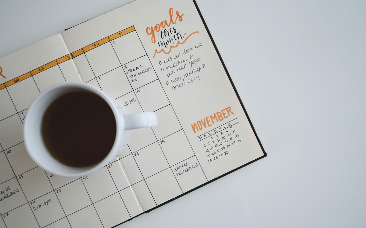 A cup of coffee sits on a monthly goals calendar. Keeping achievable goals can help you learn how to stay focused while studying.