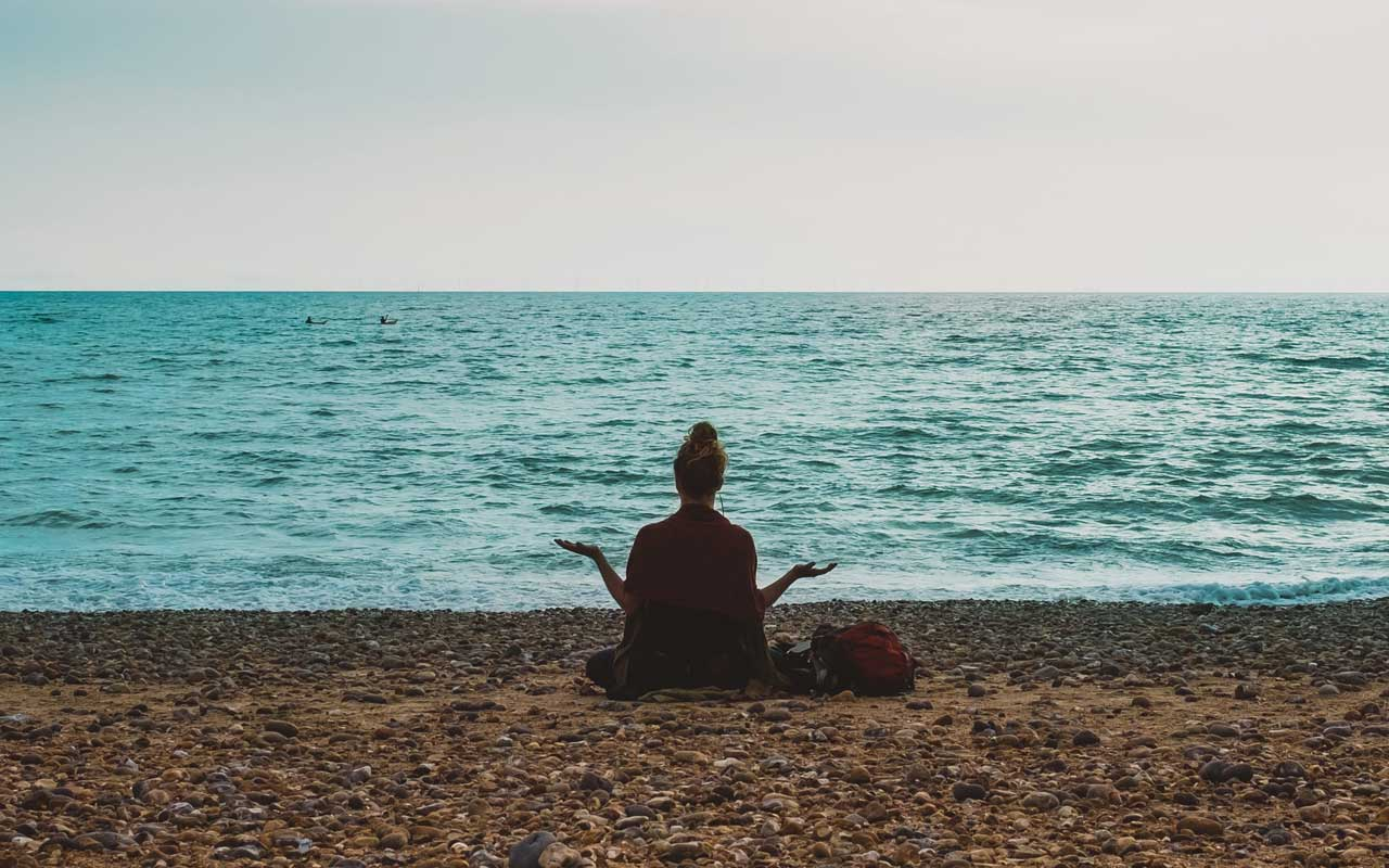 A woman meditates by the ocean. Meditation can help you concentrate on studies by clearing your mind ahead of time.