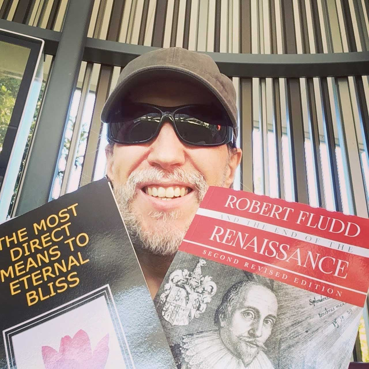 Anthony holds up two books, The Most Direct Means to Eternal Bliss and Robert Fludd and the End of the Renaissance.
