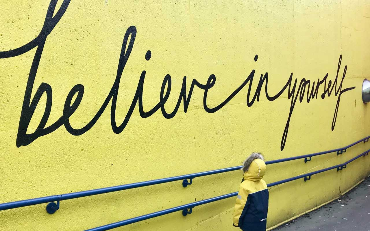 "A ""believe in yourself"" mural painted on a bright yellow wall, with a small child looking at the wall."