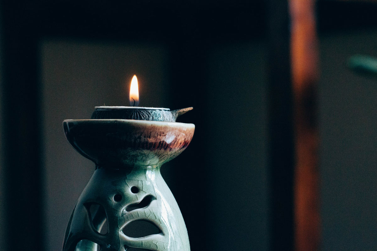 A candle burns in a pottery candle-holder. A candle can be used for the single point of focus during dharana (concentration).