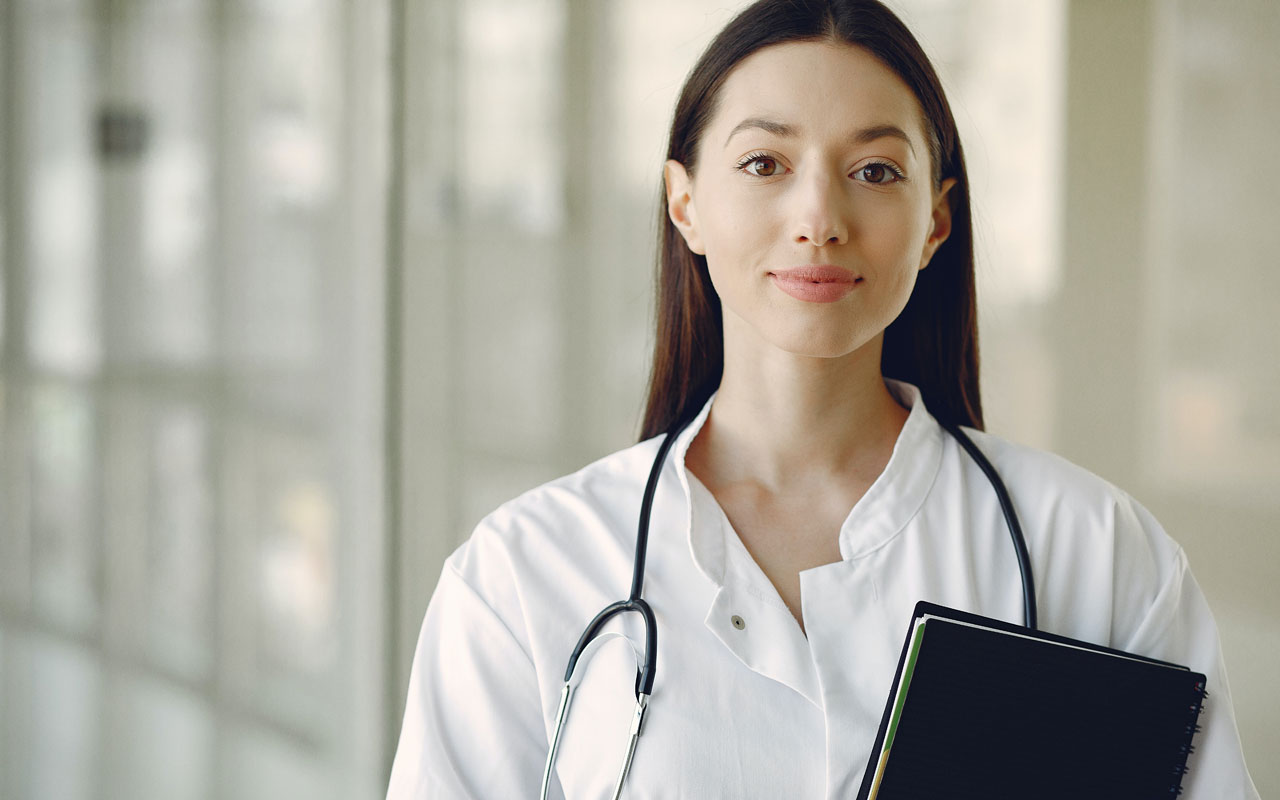 A doctor stands in a hallway with her stethoscope around her neck and a notebook in her hand.