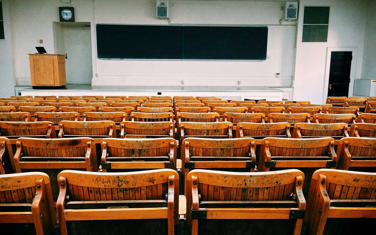 An empty college lecture hall with wooden chairs and a blackboard.