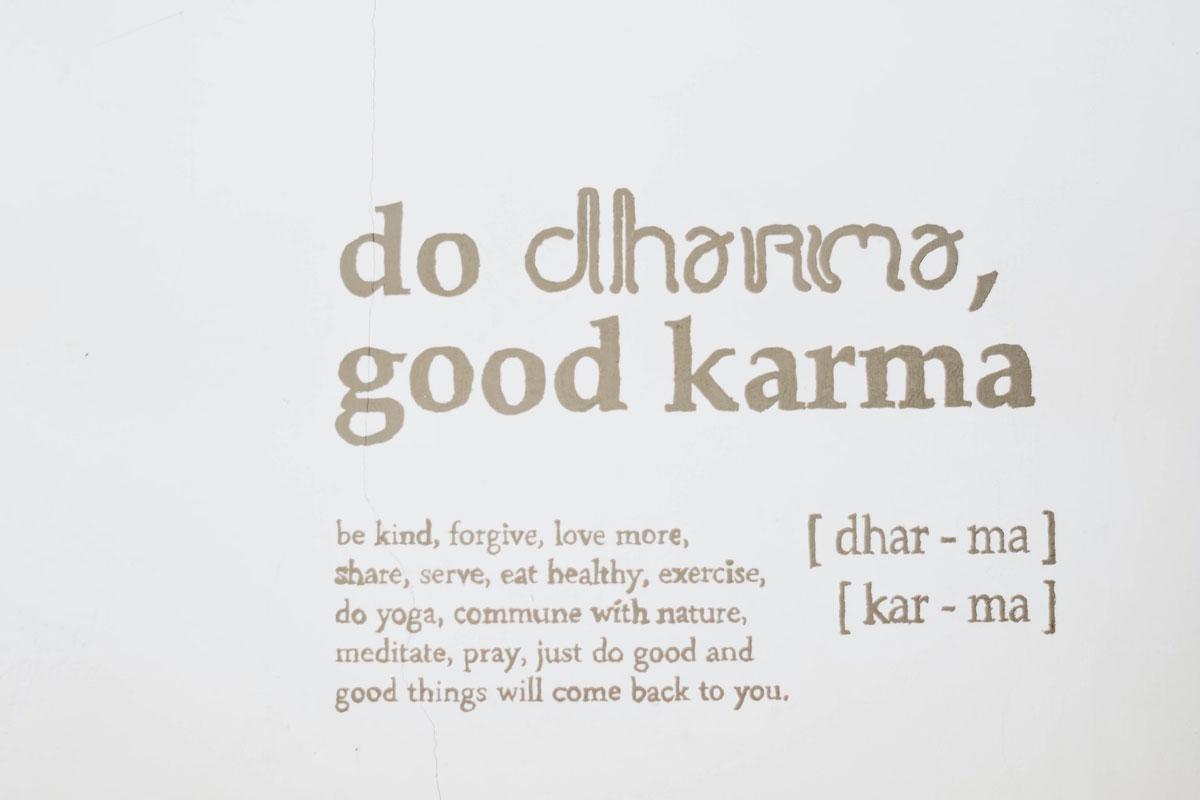 "A painted sign stating ""do dharma, good karma."""