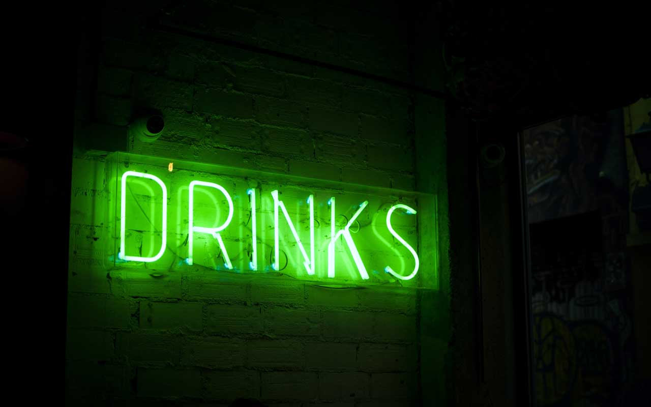 A green neon sign says DRINKS. Alcohol consumption can impair memory in adults.