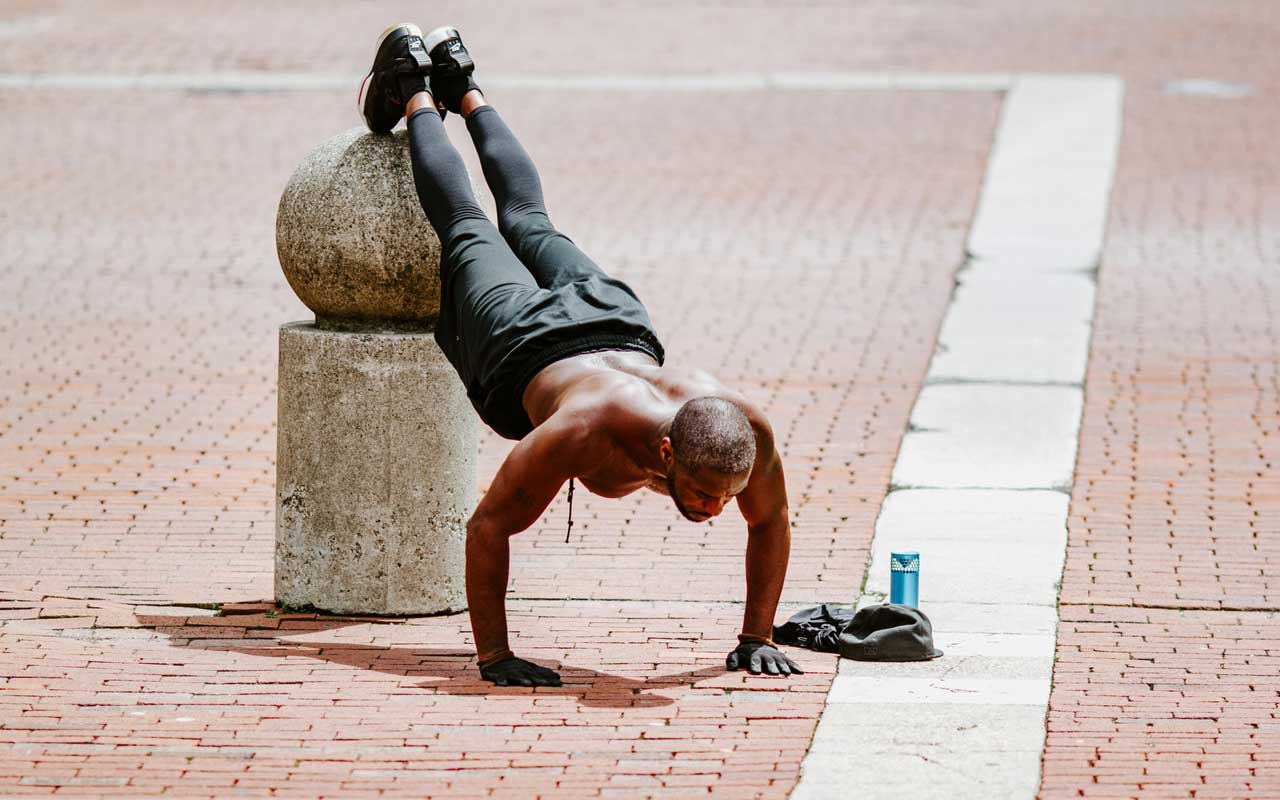 A man does pushups in an outdoor square, with his feet elevated on a concrete pier. Exercise is a natural memory enhancer.