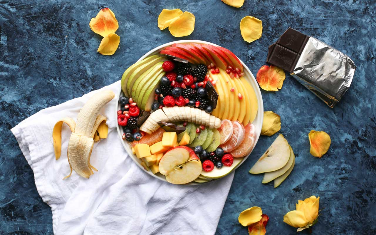 A plate full of different kinds of fruits like bananas, apples, berries, and citrus sits next to a bar of dark chocolate. Healthy foods can boost memory.