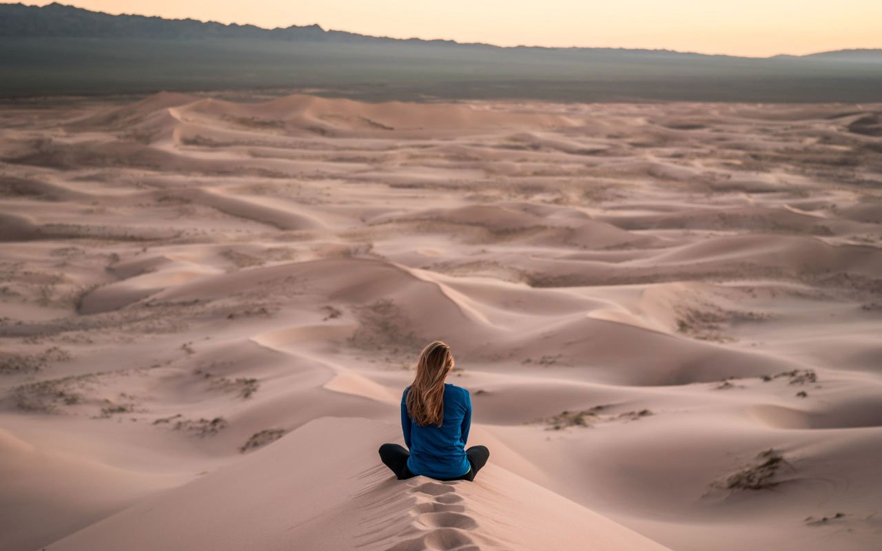 A woman sits and meditates on top of a sand dune in the desert. This could be a good setting for a guided visualization.