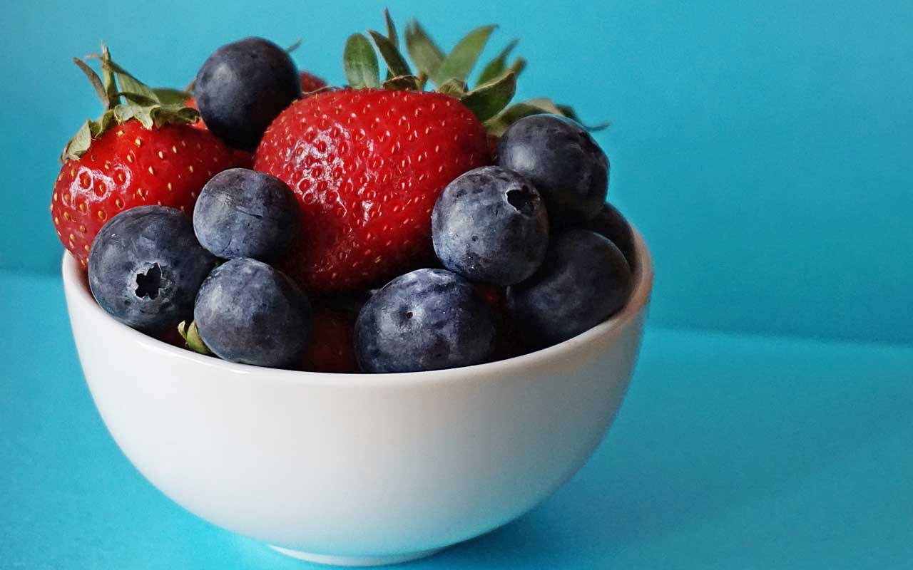 A bowl of blueberries and strawberries. Fruits like these have healthy levels of flavonoids.