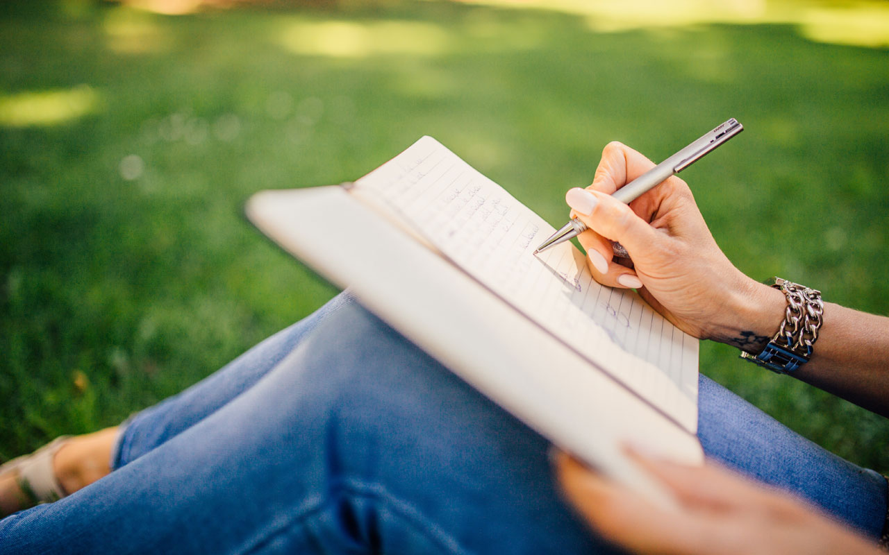 A person writes in a journal while sitting in the grass. Practices like journaling helps you gain focus.