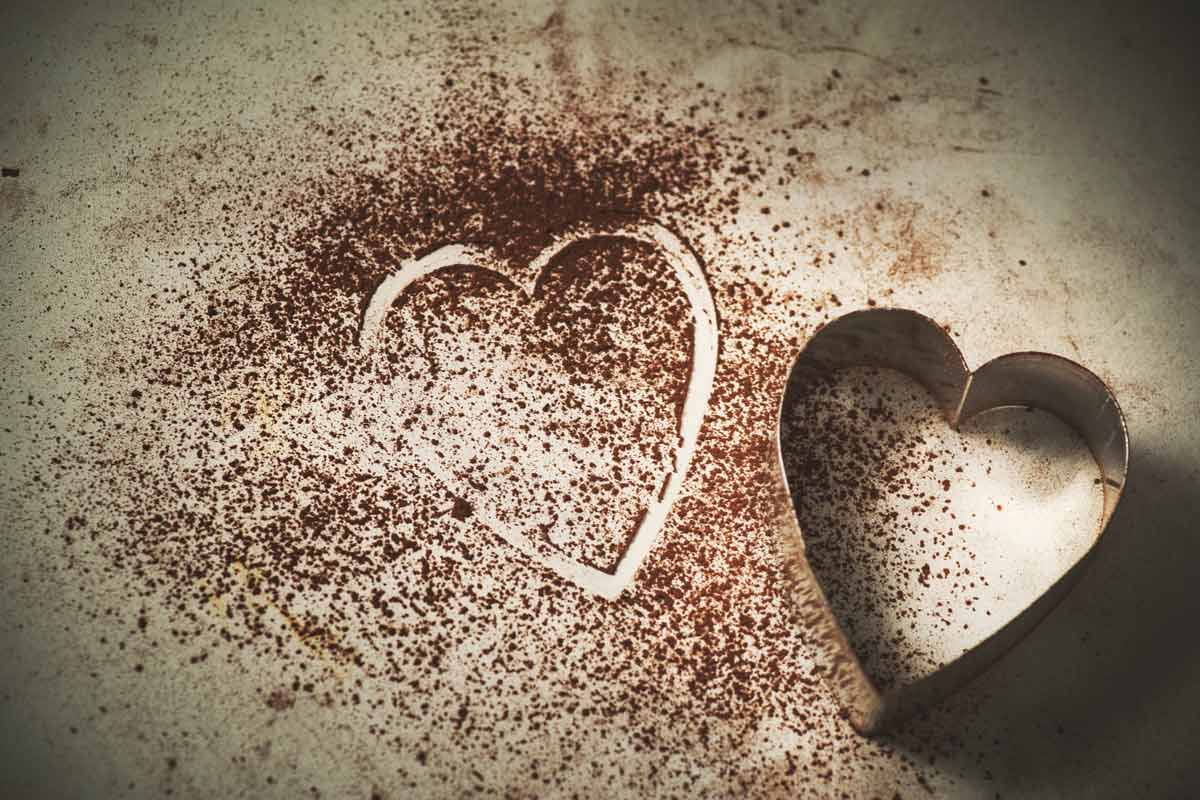 A heart-shaped cookie cutter sitting beside the outline of a heart in cocoa powder.