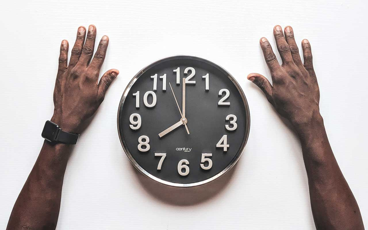 A Black man's hands next to an analog clock.