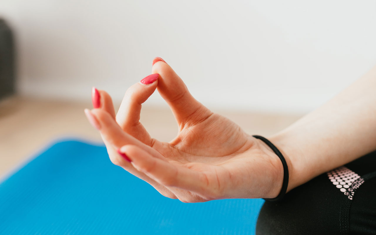 A woman's hand with red fingernails, in a yoga mudra. Meditation for mindfulness and concentration provides cognitive benefits.
