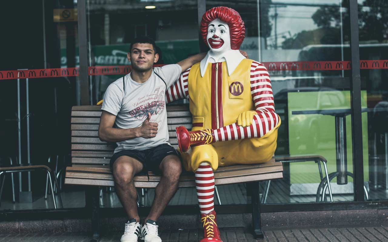 A man sits with his arm around a Ronald McDonald statue. A mnemonic strategy to remember the name
