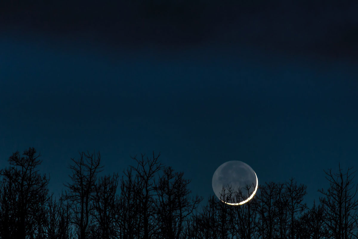 A sliver of a crescent moon hangs low on the horizon at dark, just visible over the tree line.