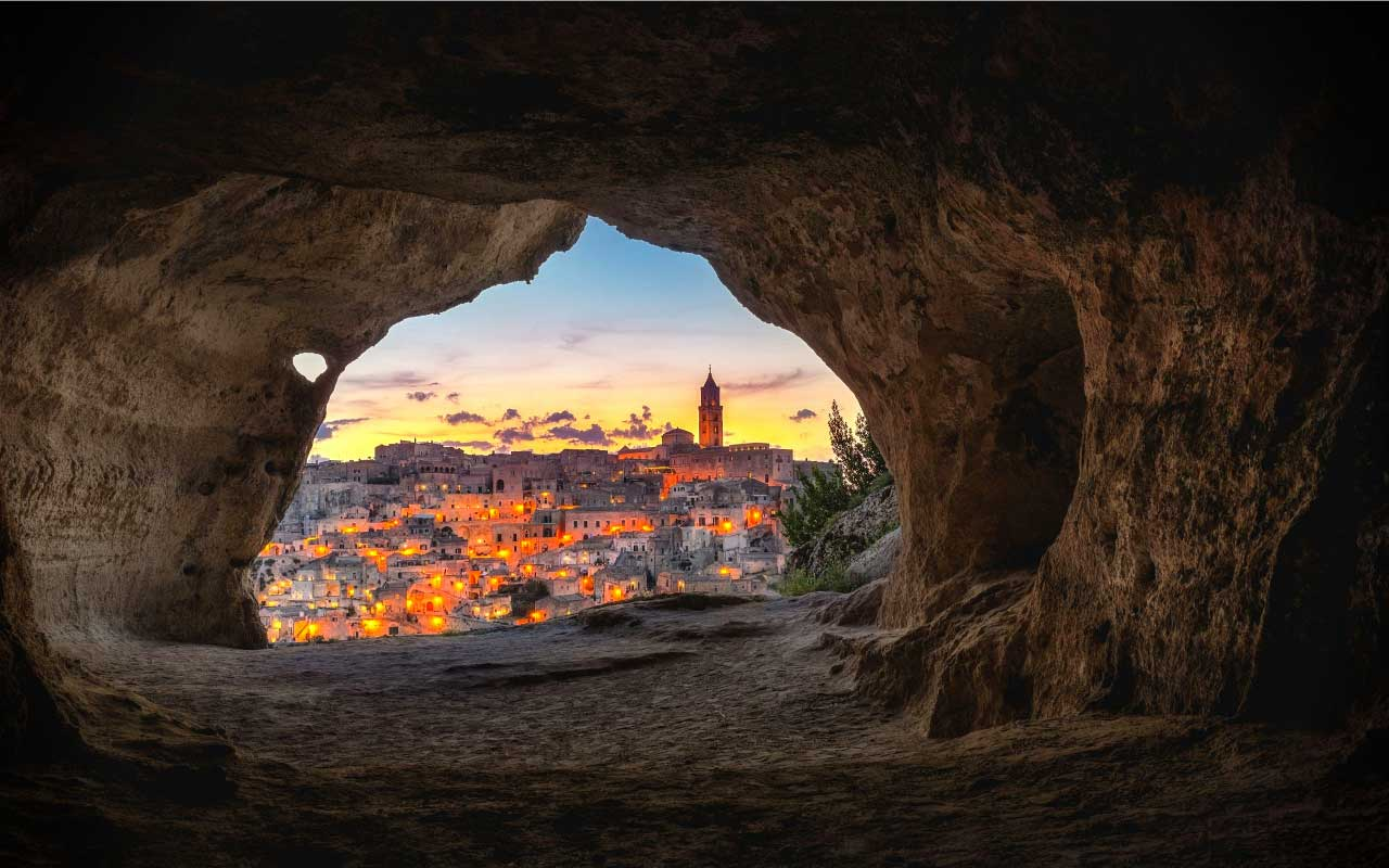 The mouth of a cave looks out over a city at dusk.