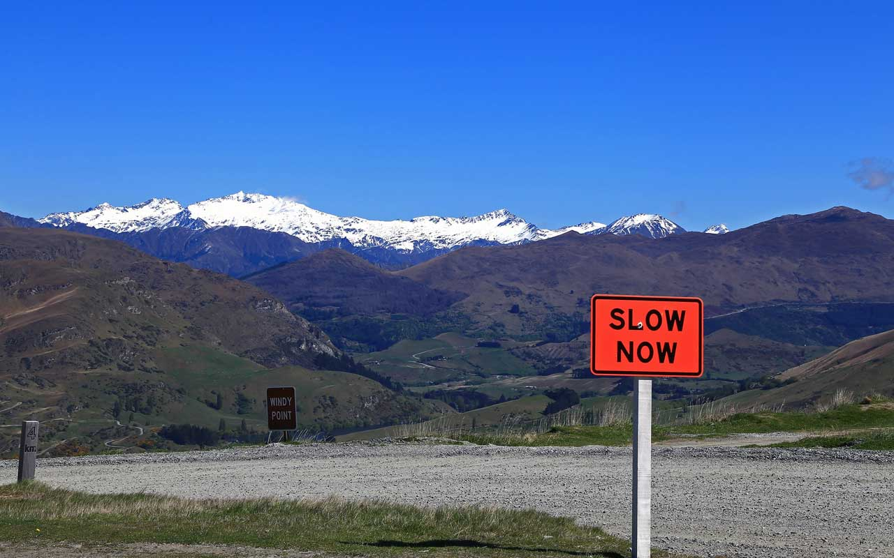 "A sign saying ""slow now"" in front of a mountain backdrop with a clear blue sky."