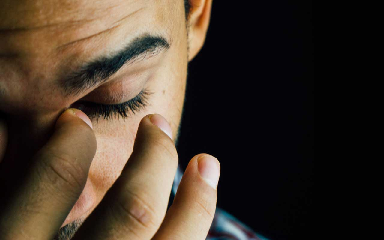 A stressed man pinches the bridge of his nose. High levels of stress are harmful to your memory.