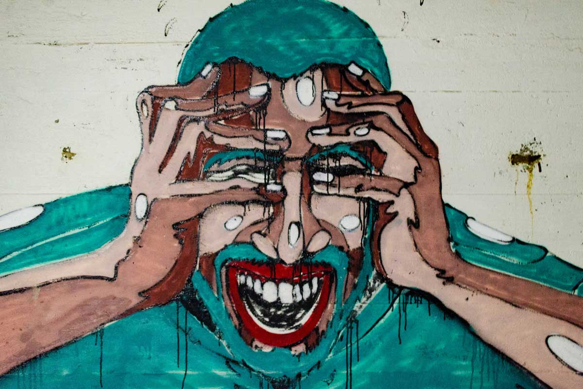 A painted mural of a stressed person holding their hands up to their head and screaming.