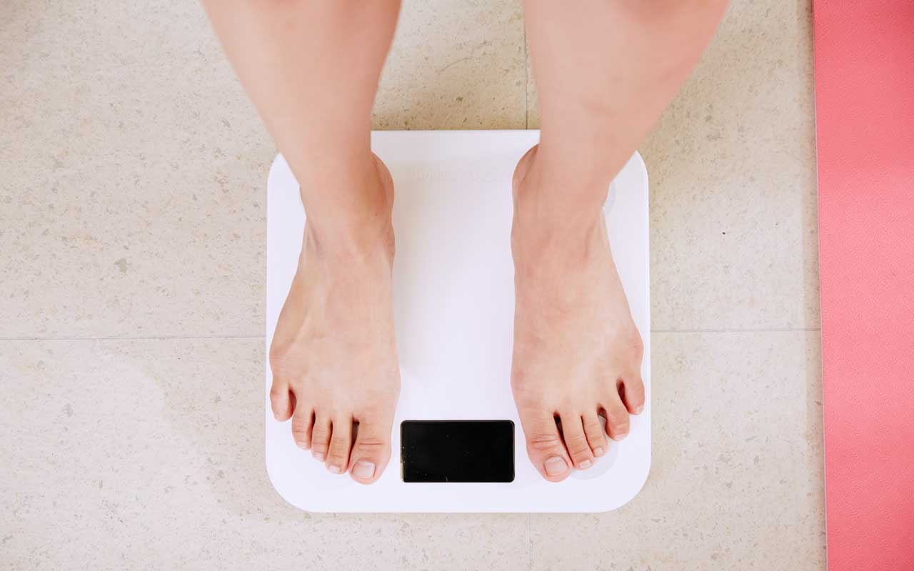 A person stands on a scale. Maintaining a healthy weight is one way to improve memory.