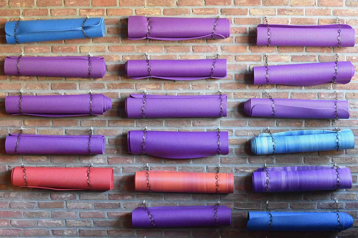 Yoga mats in multiple colors (purple, blue, and red) hang horizontally against a brick wall.