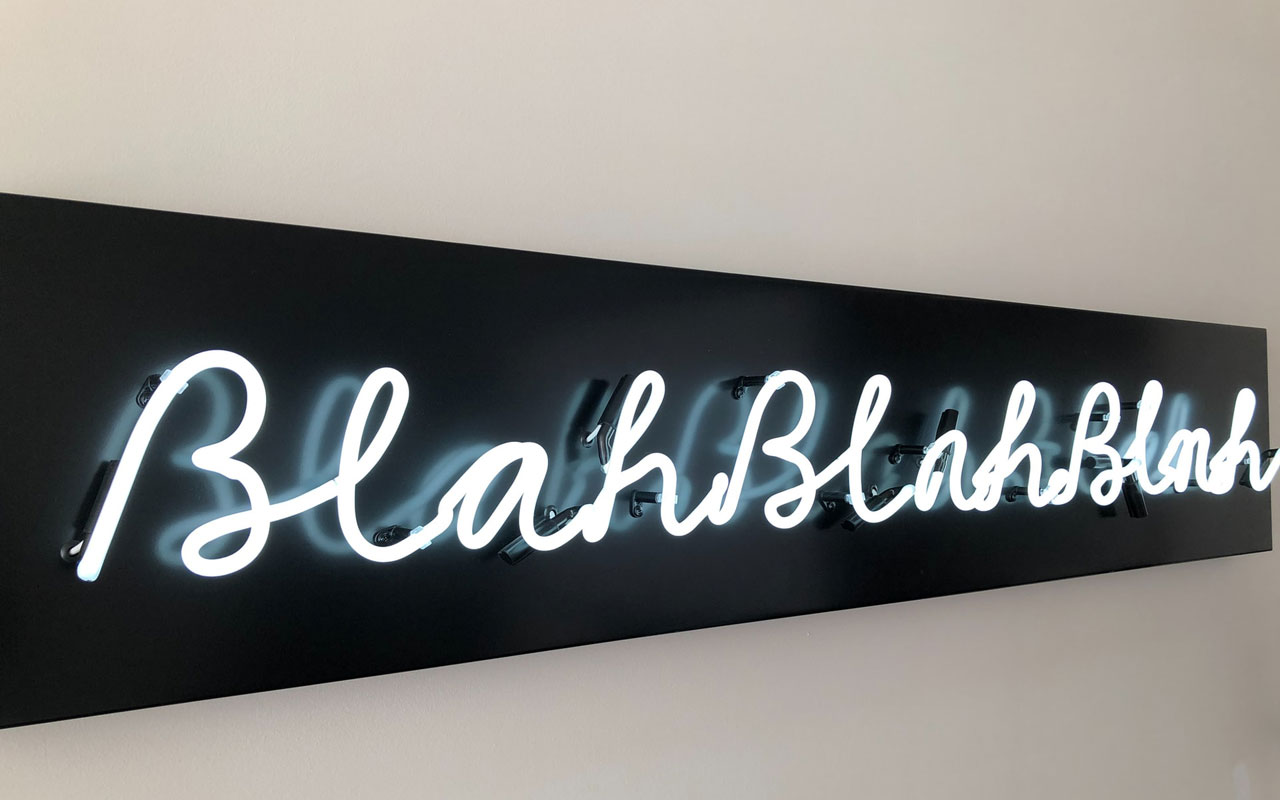 """A neon sign with white letters against a black background reads """"blahblahblah."""""""
