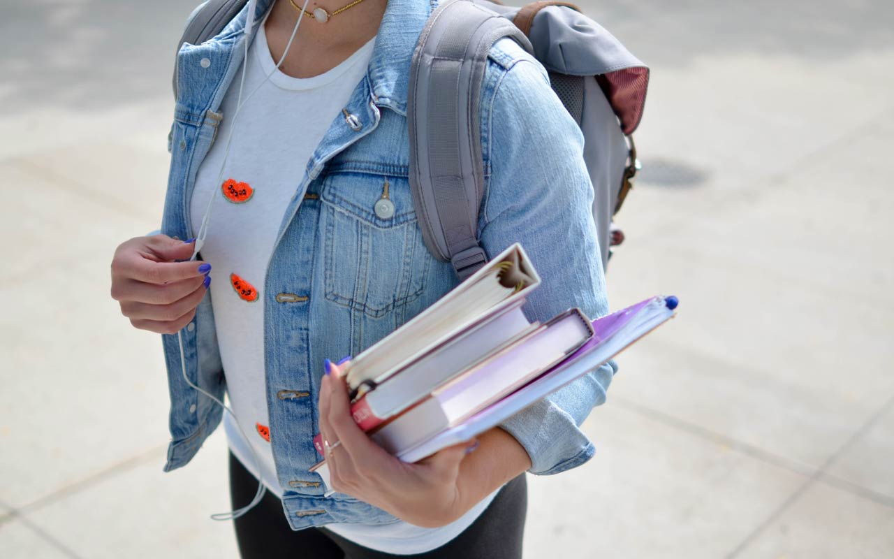 A woman wearing a denim jacket holds a stack of books as she listens to headphones.