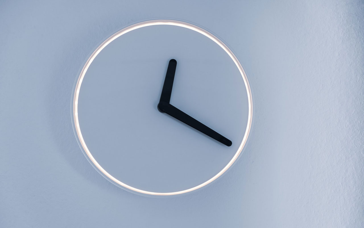 An analog clock with no numbers against a light blue wall.