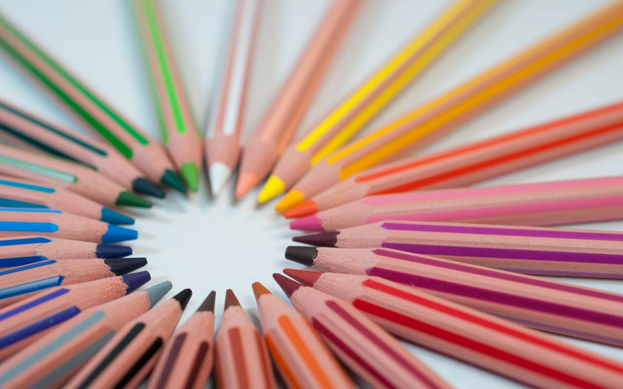 A rainbow of colored pencils are arranged in a circle. Colors are one of the language learning words you don't need to learn in context.