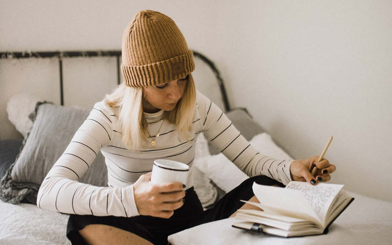 A woman wearing comfortable clothing and a beanie hat studies on her bed.