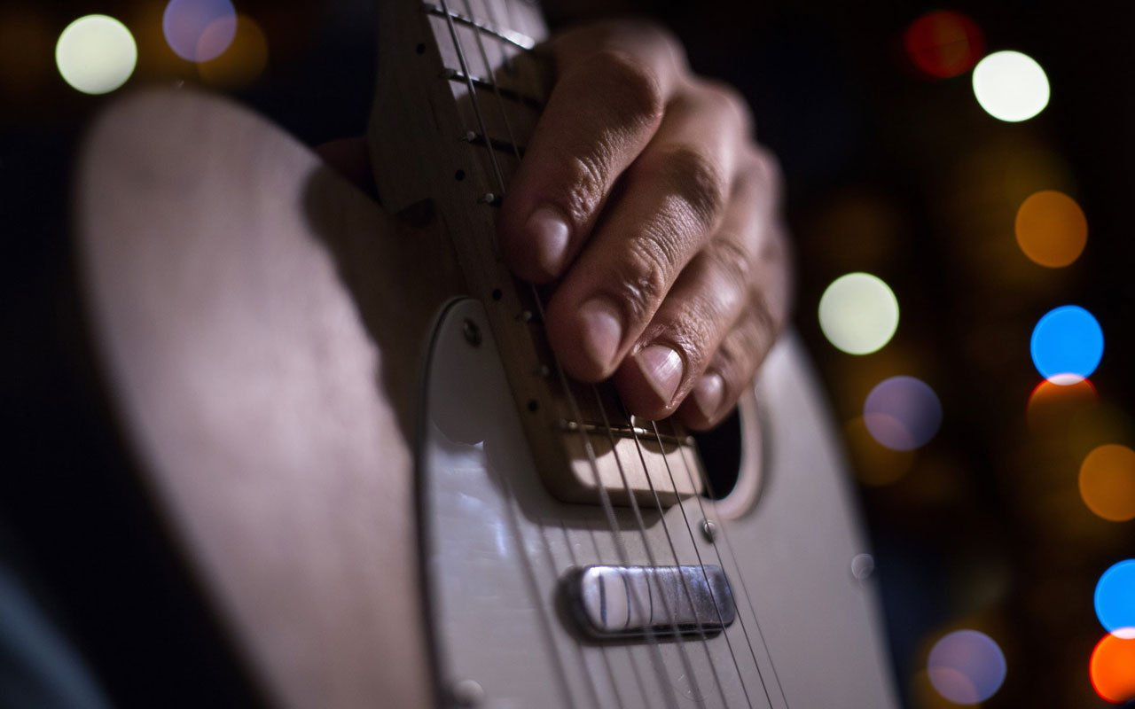 A person's hand sits on the frets of a guitar.
