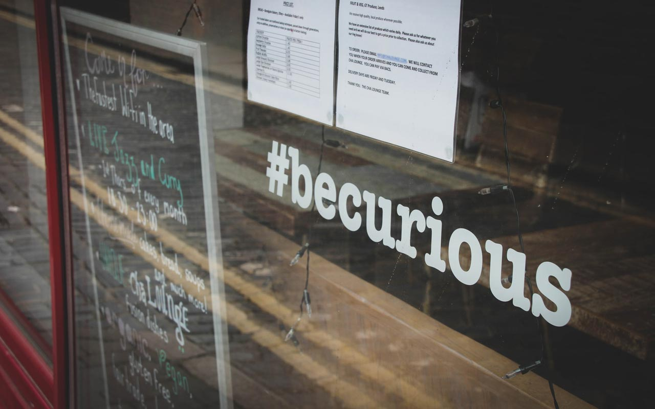 "A graphic in a restaurant window reads ""#becurious"""