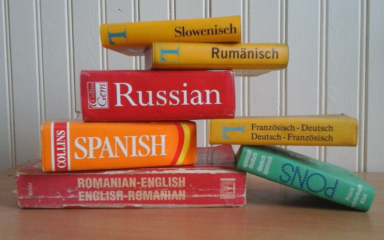 A stack of Russian, Spanish, Romanian, and German dictionaries sit on a desk.