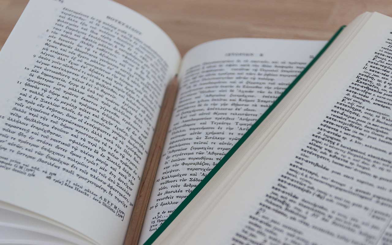 Books in two different languages lay open on a table. Becoming fluent in a language takes time.