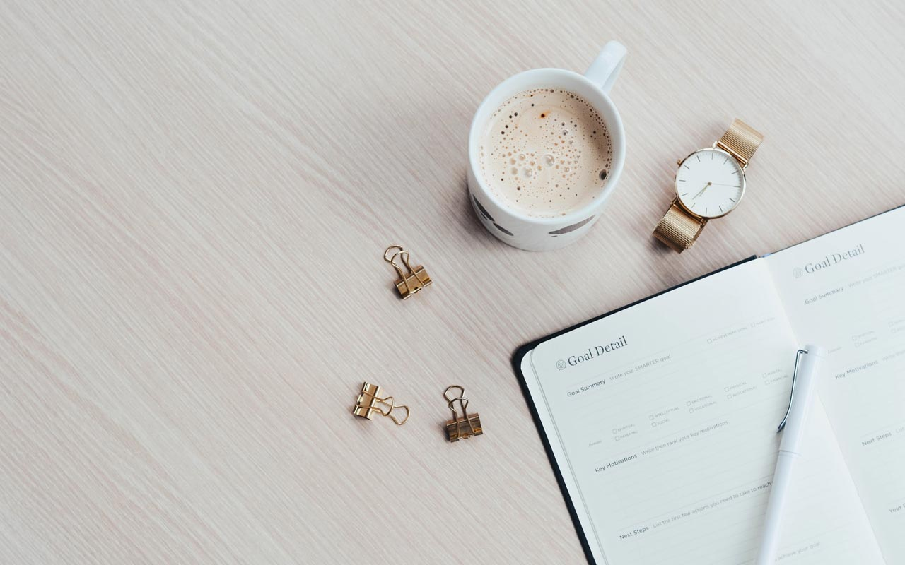 A latte and a watch sit on a desk next to a paper goal planner.