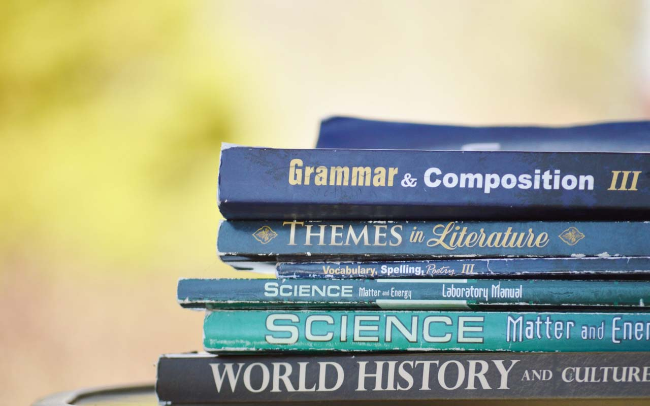 A stack of textbooks, including a Grammar & Composition book.
