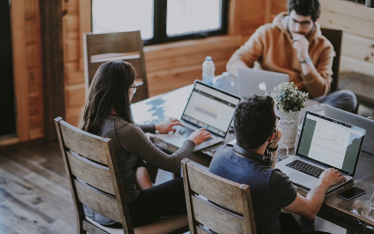 A group of three people sit around a table with their laptops. You could use an in-person accountability group to help you study effectively.