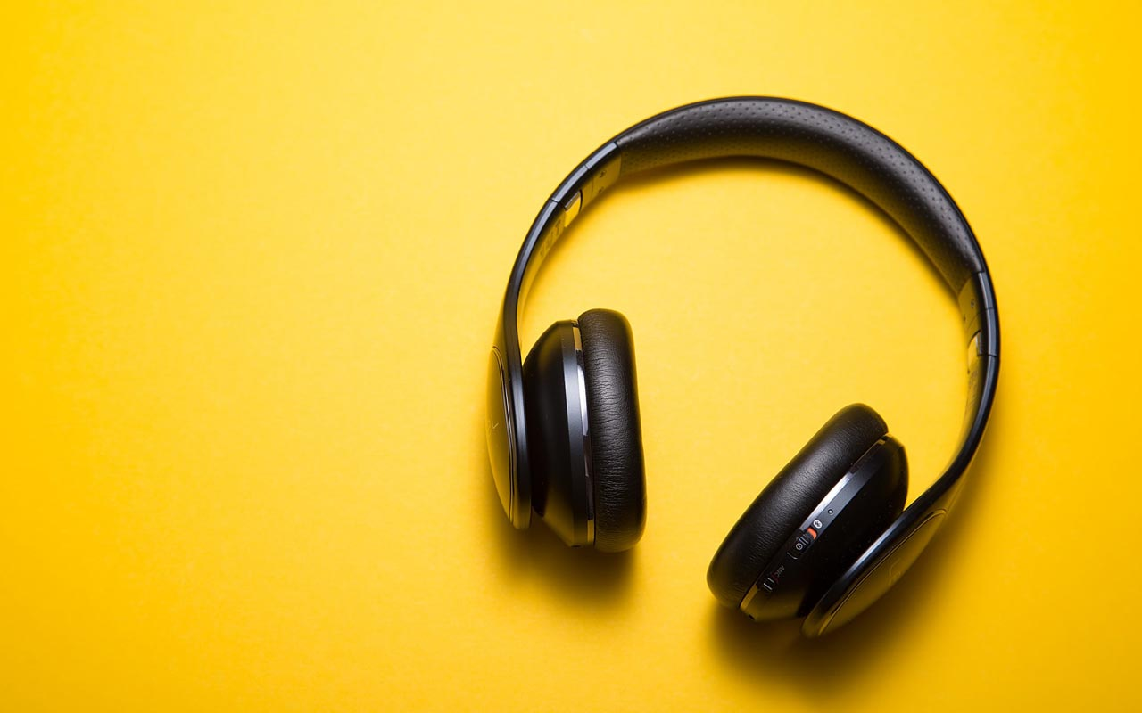 A pair of noise cancelling headphones against a bright yellow background.