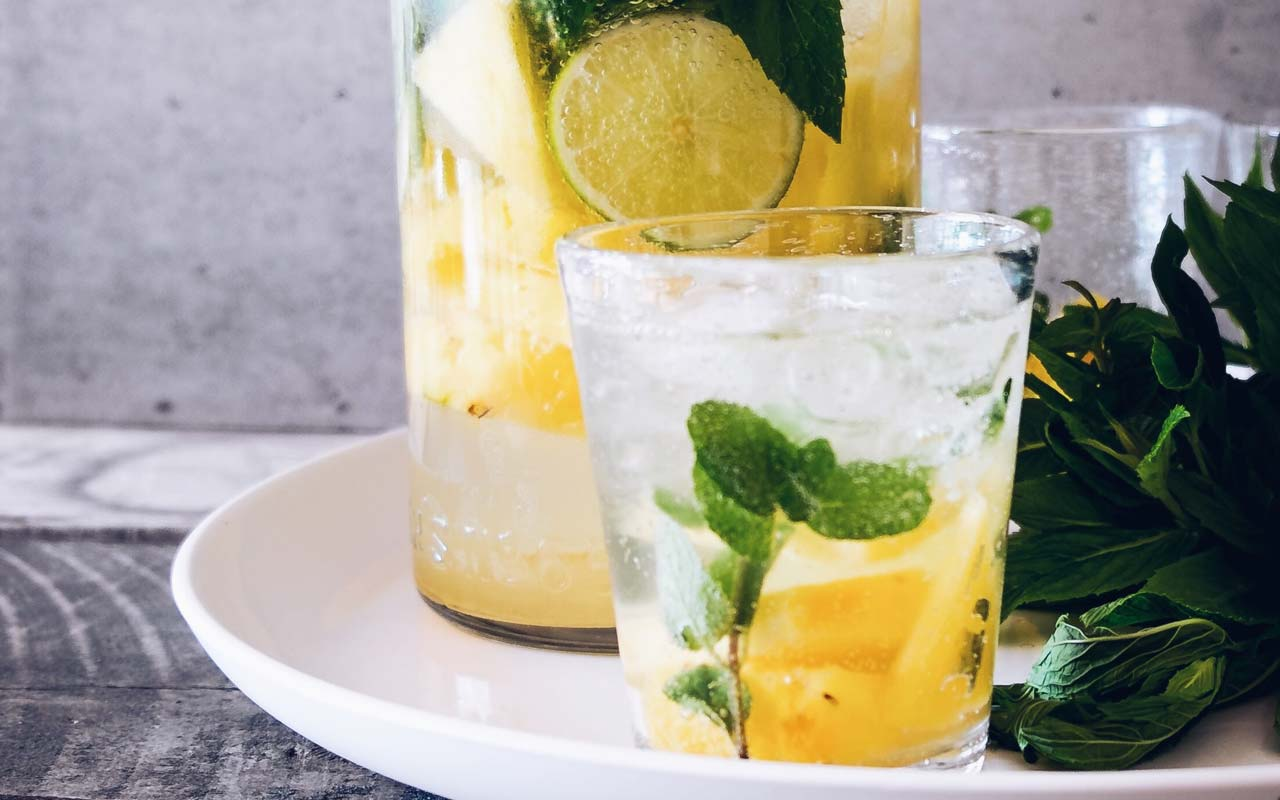 A glass of water with slices of lime, pineapple, and mint.