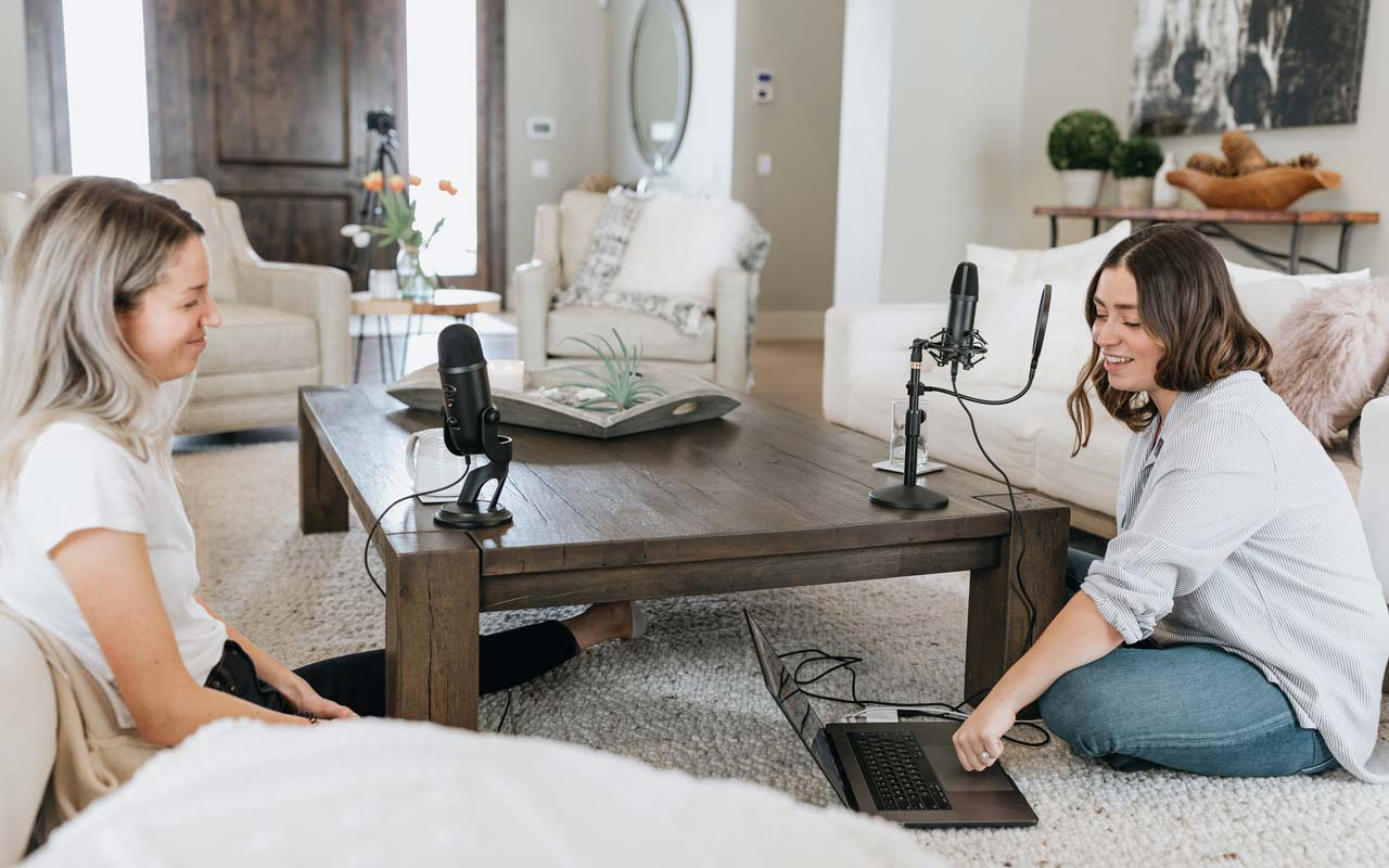 Two women sit in a living room and prepare to record a podcast episode.